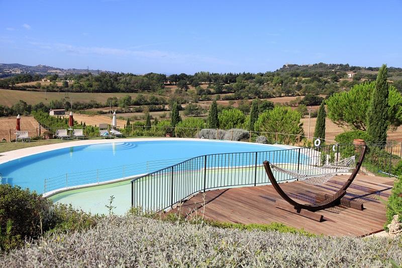 Una piscina di un albergo con vista sulle colline in Toscana